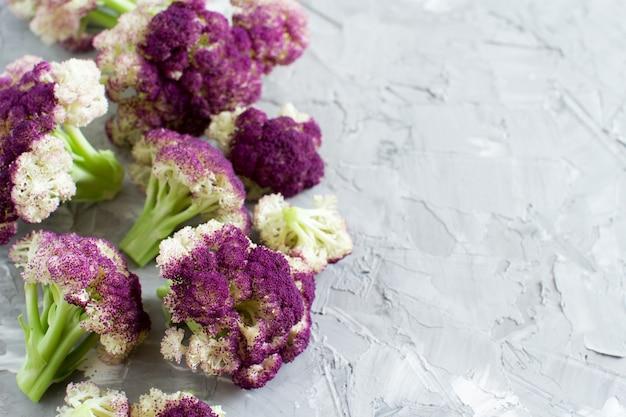 Świeży surowy fioletowy kalafior na szarej desce z bliska