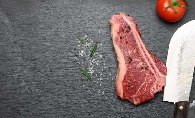 Świeży, surowy kawałek mięsa wołowego, stek z rostbefu na czarnej powierzchni, widok z góry. marmurkowy kawałek mięsa nowy jork, miejsce na kopię