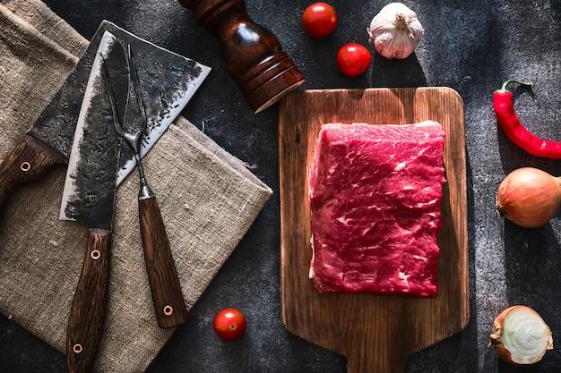 Świeży, surowy kawałek wołowiny z tasakiem do mięsa dla rzeźnika. widok z góry.