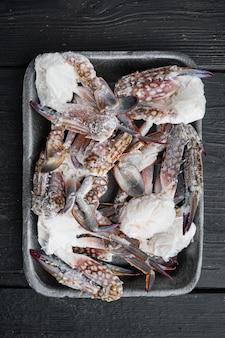 Świeży surowy krab kwiatowy lub niebieski krab mrożony zestaw, w plastikowej tacy, na tle czarnego drewnianego stołu, płaski widok z góry