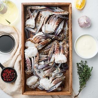 Świeży surowy krab, niebieski krab, zestaw krabów kwiatowych, w drewnianym pudełku, na białym tle, widok z góry płaski
