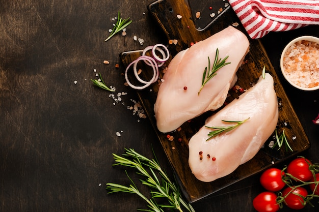 Świeży surowy kurczak mięso polędwicowy z solą, pieprzem, cebulą na drewnianym nieociosanym tle