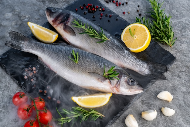 Świeży, surowy labraks z cytrynowym pomidorem i przyprawami na czarnym kamiennym talerzu z lodowatą, mroźną mgłą parową. świeże owoce morza w koncepcji rynku.
