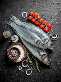 Świeży surowy labraks z przyprawami i pomidorami na gałęzi na czarnym rustykalnym stole