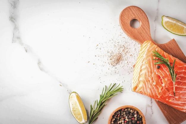 Świeży surowy łosoś rybny, filet stekowy, z przyprawami, limonką, rozmarynem, solą