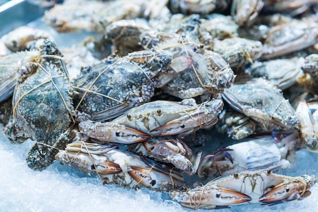 Świeży surowy niebieski krab pływacki na lodzie na sprzedaż na rynku owoców morza.