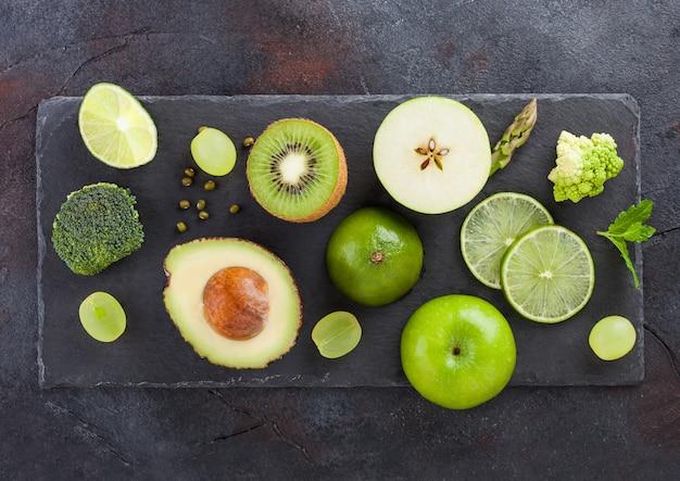 Świeży surowy organicznie zielony stonowany owoc i warzywo. awokado, limonka, jabłko, kiwi i winogrona z brokułami i kalafiorem. widok z góry