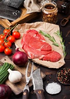 Świeży surowy organiczny plasterek duszącego fileta stekowego na papierze rzeźniczym z widelcem i nożem na ciemnym drewnianym