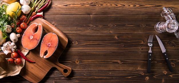 Świeży surowy rybi łososiowy stek z ziele i warzywami na drewnie