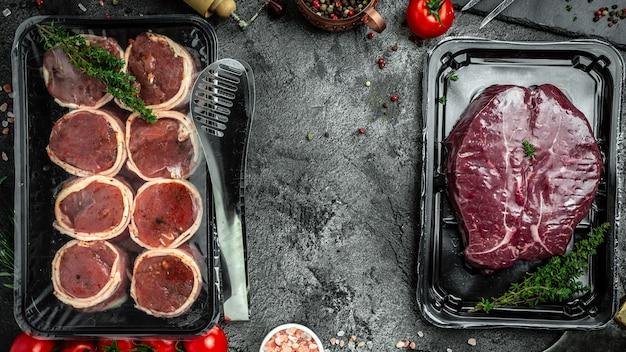 Świeży, surowy stek dojrzewający na sucho w próżniowym filecie steki z miniona zawinięty w bekon. produkty mięsne pakowane. surowy stek filet mignon. baner, miejsce przepis menu na tekst, widok z góry.