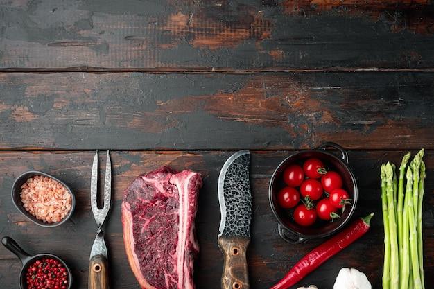 Świeży, surowy stek klubowy z dodatkiem soli, czosnku i ziół, na starym ciemnym drewnianym stole
