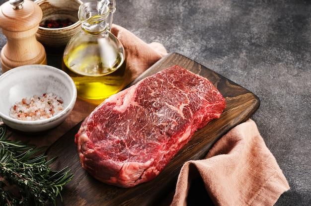 Świeży surowy stek nowojorski na drewnianej desce na szarym tle z solą, pieprzem i oliwą z oliwek, widok z góry, miejsce.