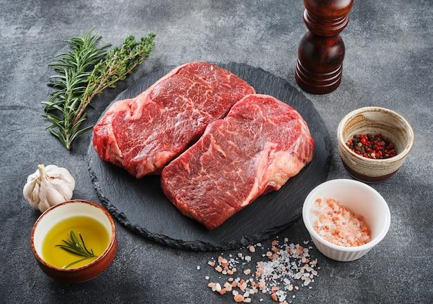 Świeży surowy stek nowojorski na kamiennej desce na szarym tle z solą, pieprzem i oliwą z oliwek, widok z góry.