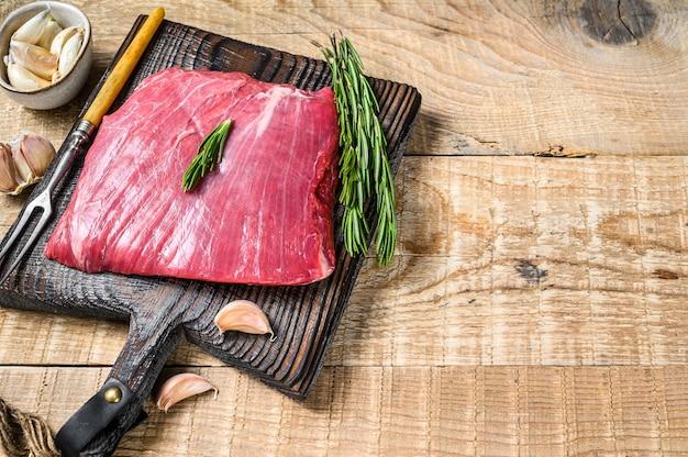 Świeży surowy stek wołowy lub bavette z marmurkowym mięsem z rozmarynem. drewniane tło. widok z góry. skopiuj miejsce.