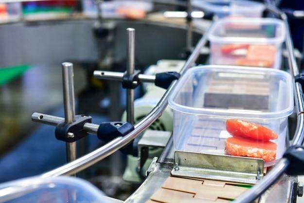 Świeży surowy stek wołowy w pudełkach przeniesiony na automat do pakowania.