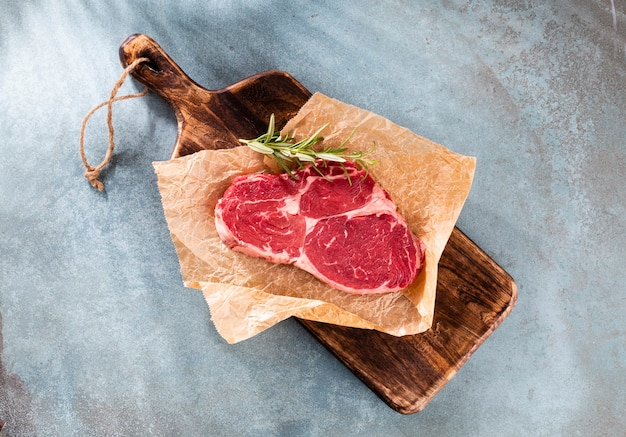 Świeży, surowy stek z antrykotu na drewnianej desce do krojenia, ze szpinakiem, soczewicą i rozmarynem w stylu rustykalnym.