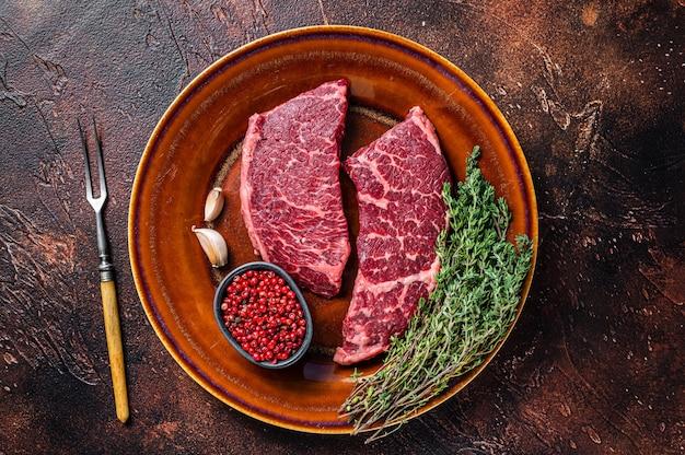 Świeży surowy stek z denver lub top blade na rustykalnym talerzu z tymiankiem