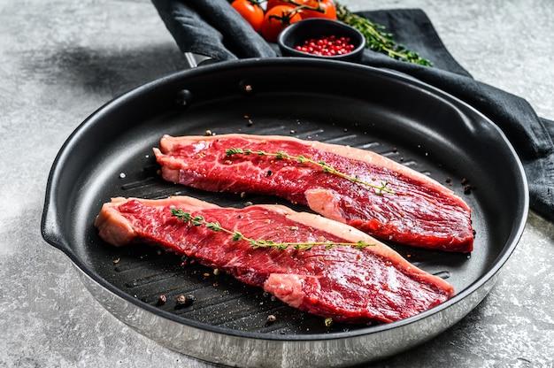 Świeży surowy stek z polędwicy na patelni grillowej. widok z góry
