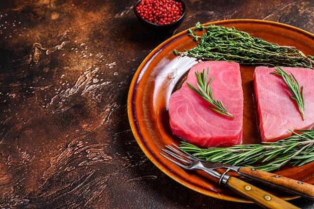 Świeży surowy stek z tuńczyka z rozmarynami. ciemne tło. widok z góry. skopiuj miejsce.
