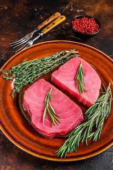 Świeży surowy stek z tuńczyka z rozmarynami. ciemne tło. widok z góry.