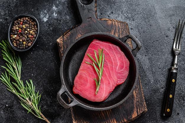 Świeży surowy stek z tuńczyka z rozmarynem na patelni. czarne tło. widok z góry.