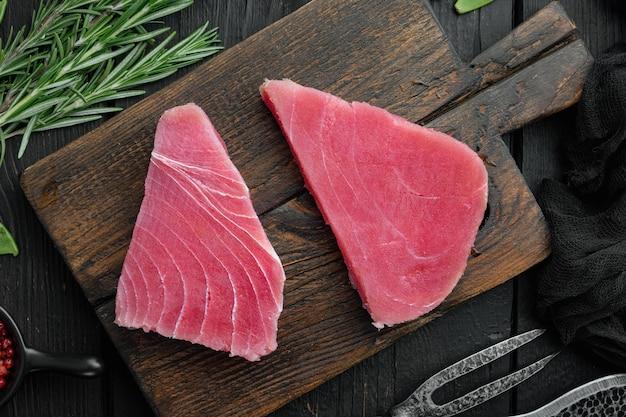 Świeży surowy stek z tuńczyka z zielonym groszkiem, sezamem i szczypiorkiem, na drewnianej desce do krojenia, na czarnym drewnianym tle, płaski widok z góry