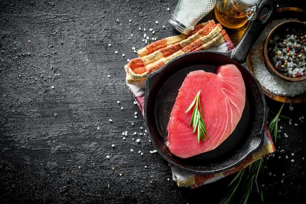 Świeży surowy tuńczyk na patelni na serwetce z rozmarynem i przyprawami. na czarnym tle rustykalnym