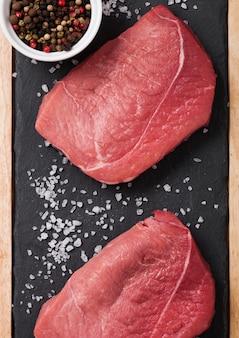 Świeży surowy wołowina stku mięso na kamiennej kuchni desce z pieprzem na czarnym tle