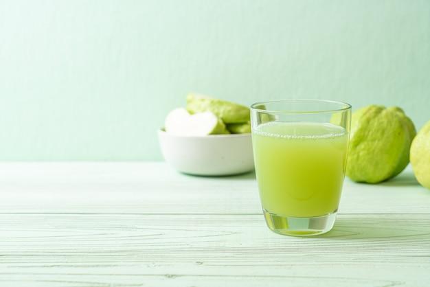 Świeży szklany sok z guawy ze świeżymi owocami guawy na stole z drewna