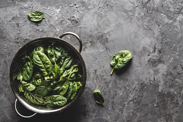 Świeży szpinak mini w durszlaku na starym betonowym stole. zdrowa żywność, produkt ekologiczny. wegańskie