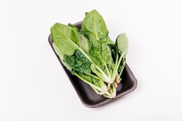 Świeży szpinak zielony pakowany na białym tle. żywność ekologiczna, zdrowy styl życia