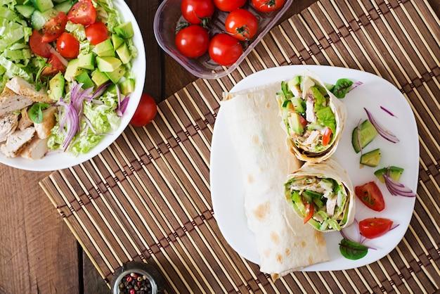 Świeży tortilla zawija z kurczakiem i świeżymi warzywami na talerzu. widok z góry