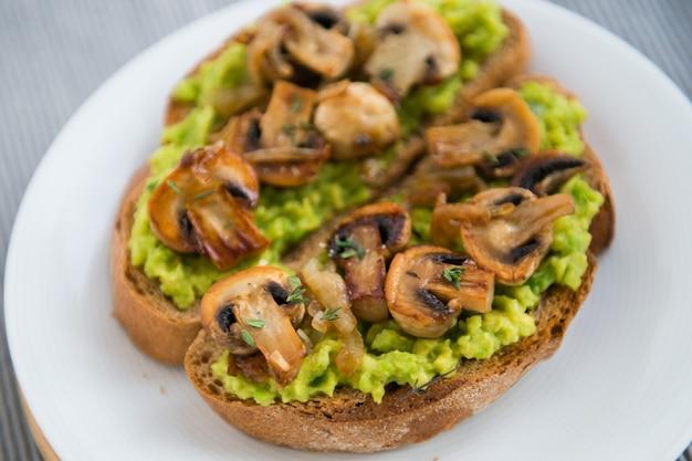 Świeży tost z awokado i grzybami