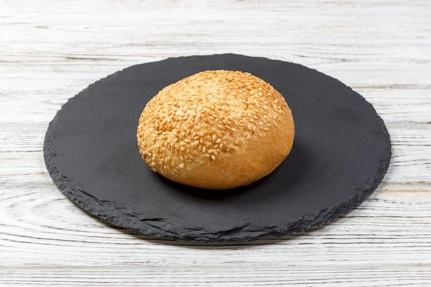 Świeży upieczony chleb lub bułka z sezamem i słonecznikiem na desce łupkowej
