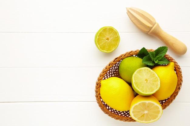 Świeży wapno i cytryna w koszu z sokowirówki cytrusowej trzymać na białym tle. składnik preparatu do gotowania z limonką i cytryną.