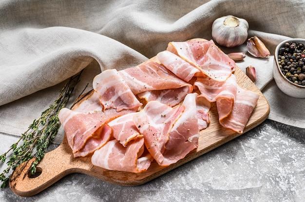 Świeży wieprzowina bekon na desce do krojenia. organiczne surowe mięso wieprzowe. szare tło. widok z góry.