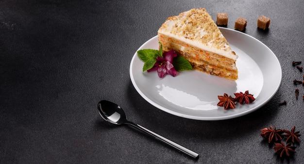 Świeży wyśmienicie marchwiany tort z śmietanką na ciemnym tle. ciasto marchewkowe z bitym lukrem