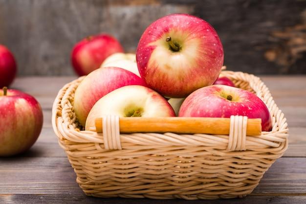 Świeży zbiór jabłek. motyw natury z czerwonymi jabłkami w koszu na drewnianym stole