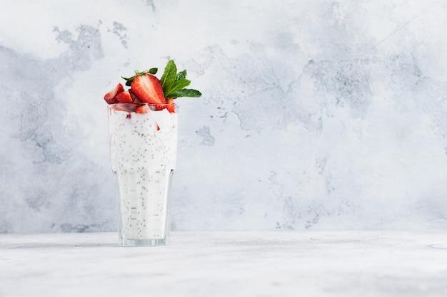 Świeży zdrowy jogurt mleczny z nasionami chia i truskawkami w szklanej zlewce na szarej betonowej powierzchni