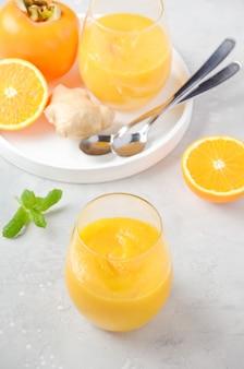 Świeży zdrowy koktajl z persimmon, pomarańczy i imbiru.