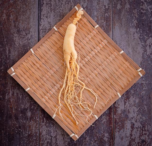 Świeży żeń-szeń na bambusowym splocie z drewnianym stołem