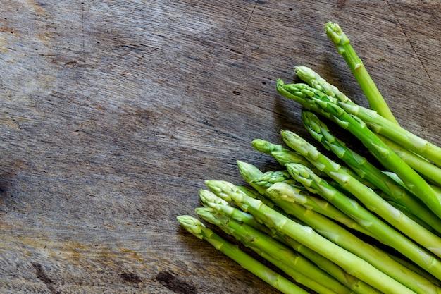 Świeży zielony asparagus na drewnianym tle