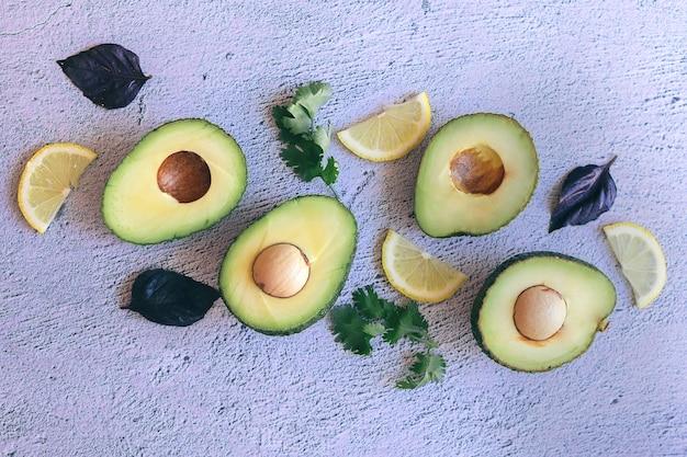 Świeży zielony cały, przekrojony na pół i pokrojony w plasterki awokado i cytryna, kolendra i bazylia na białym tle na kamiennym tle
