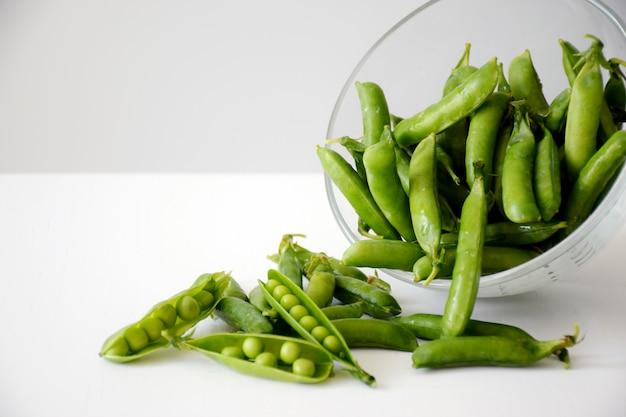 Świeży zielony groszek i strąki w szklanej misce na białym stole