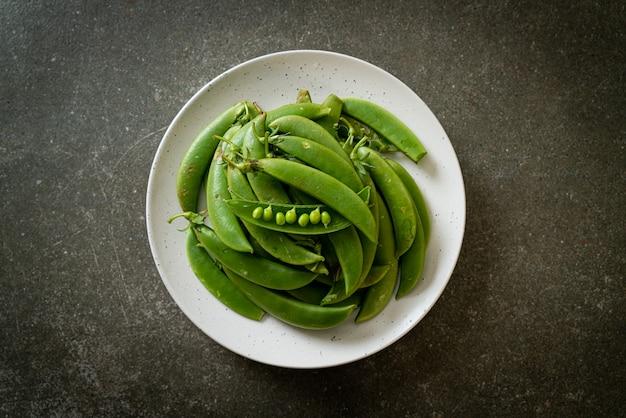 Świeży zielony groszek na białym talerzu