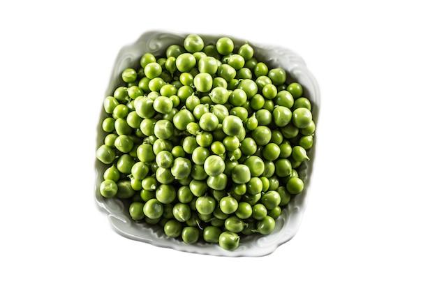 Świeży zielony groszek w białej misce na białym tle - widok z góry.