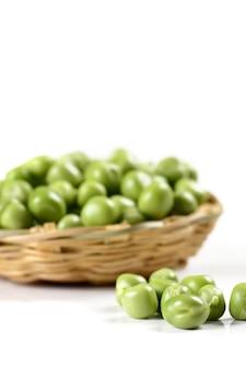 Świeży zielony groszek w koszu na białej powierzchni
