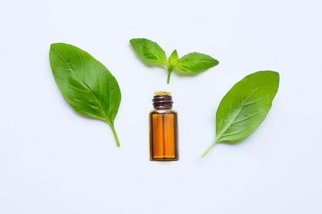 Świeży zielony liść bazylii z niezbędnym oi; na białym tle