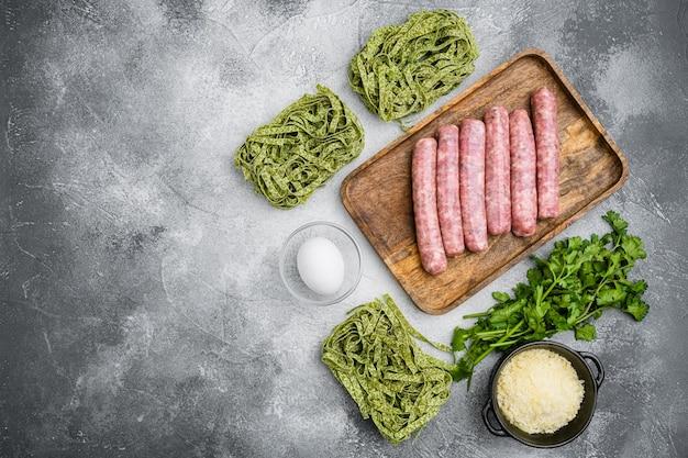 Świeży zielony makaron i kiełbaski, na szarym tle kamiennego stołu, płaski widok z góry, z miejscem na kopię tekstu