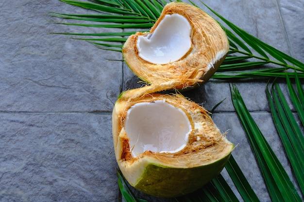 Świeży zielony owoc kokosa pokrojony na pół i liście kokosa